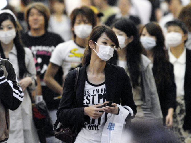 People wear face masks at a shopping street in Kobe, western Japan.