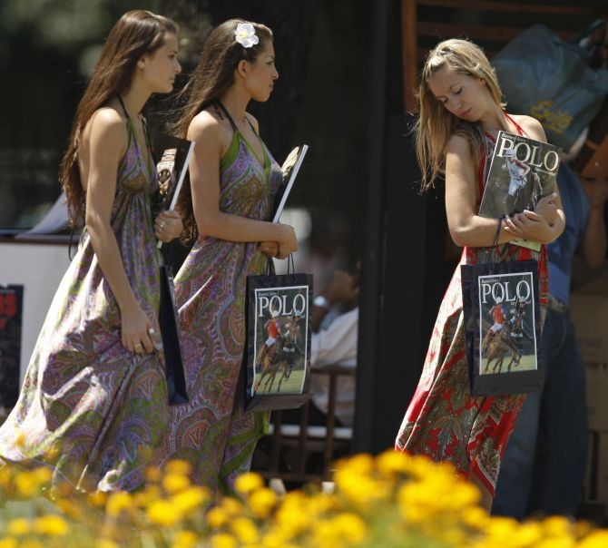 Woman walk with polo magazines at the Campo Argentino de Polo in the Buenos Aires neighborhood of Palermo.