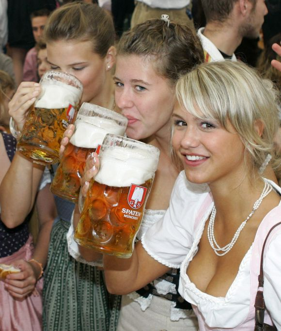 Girls in traditional Bavarian clothes toast with one-litre beer mugs during the opening day of the Oktoberfest in Munich.