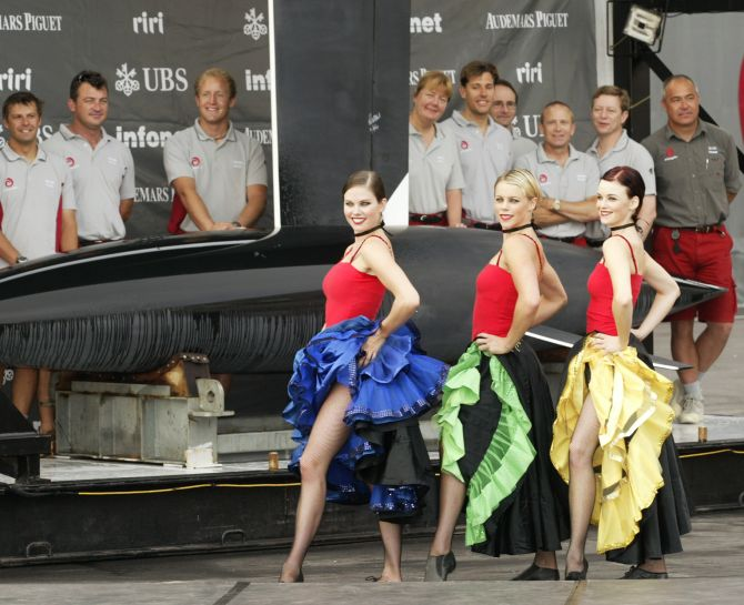 Dancing girls and the design team participate in the unveiling of the Alinghi race boat.