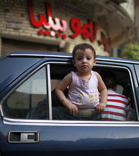 A child looks outside a car window in Cairo.