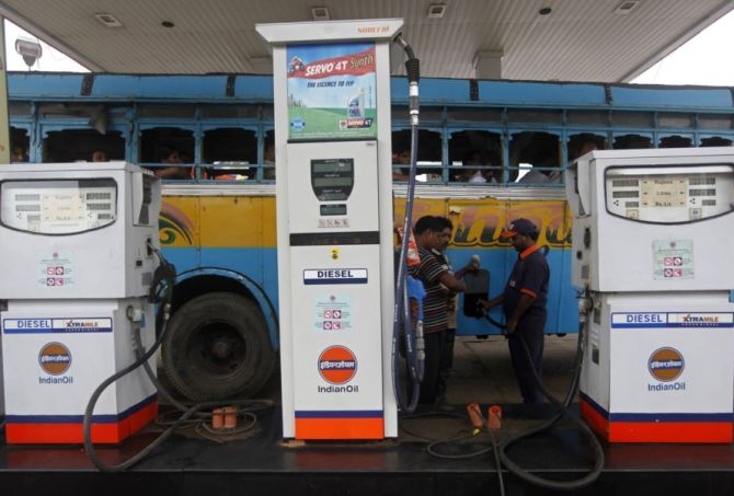An employee fills diesel in a public bus at a fuel station in Kolkata.