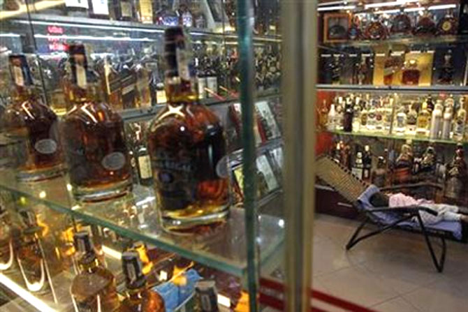 A child sleeps at a shop selling whisky in Hanoi.