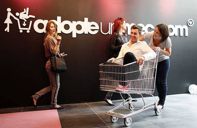 A single woman pushes a bachelor who rides in a shopping trolley at the 'adopt-a-guy' (adopte-un-mec) store in Paris, France.