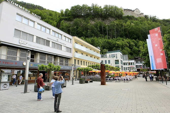 A woman takes a picture of Vaduz Castle in the town centre of Liechtenstein's capital Vaduz.