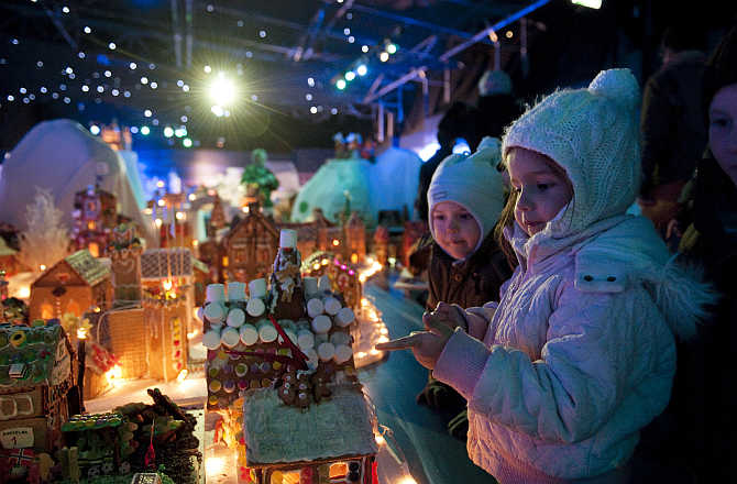 Children look at a gingerbread town consisting of buildings, boats, bridges and other structures, in Bergen, Norway.