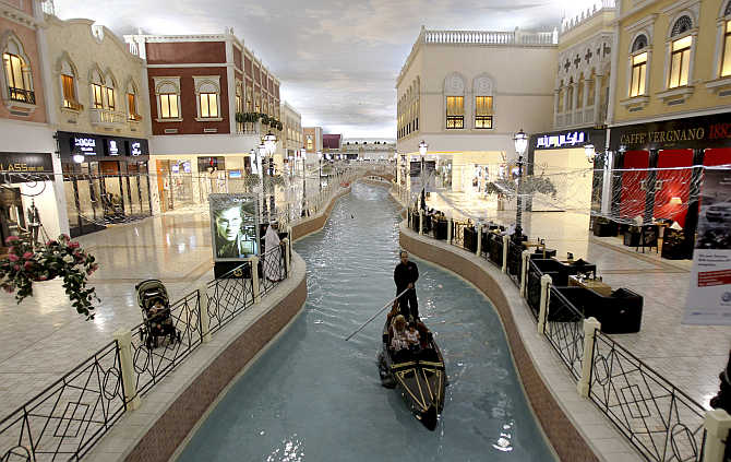 A family takes a sampan ride on a canal inside Villagio Mall, a popular shopping area in Doha, Qatar.