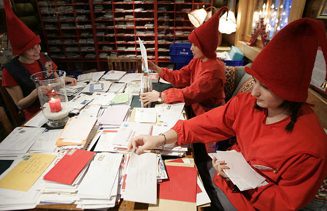 People dressed as elves read letters from around the world which were sent to Santa Claus at the Santa Claus' Post Office on the Arctic Circle near Rovaniemi, northern Finland.
