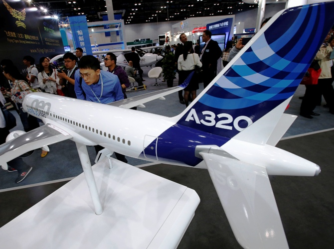 A visitor looks at a miniature model of an Airbus A320 at an Aviation Expo