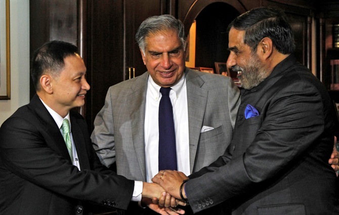 Commerce Minister Anand Sharma (R) shakes hands with Singapore Airlines Ltd (SIA) Chief Executive Officer Goh Choon Phong as Tata Group Chairman Emeritus Ratan Tata (C) looks on.