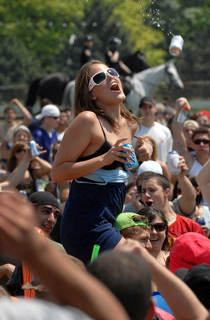 A woman dodges a flying beer can at Pimlico Race Course in Baltimore, Maryland, United States.