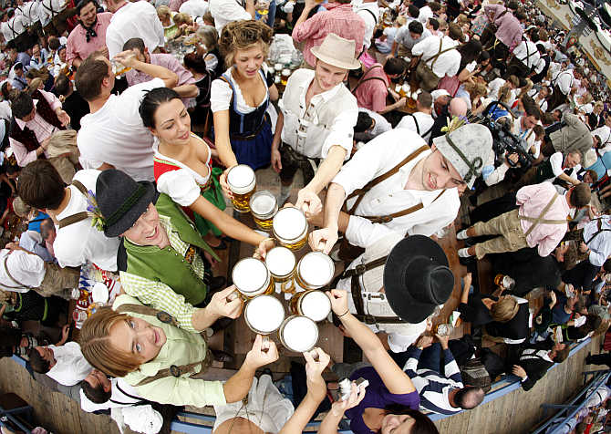People toast with beer mugs at the Oktoberfest in Munich, Germany.