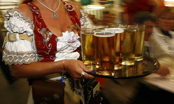 A waitress carries a tray of wine during the Duerkheimer Wurstmarkt, the world's biggest wine fest, in the southwestern German town of Bad Duerkheim.