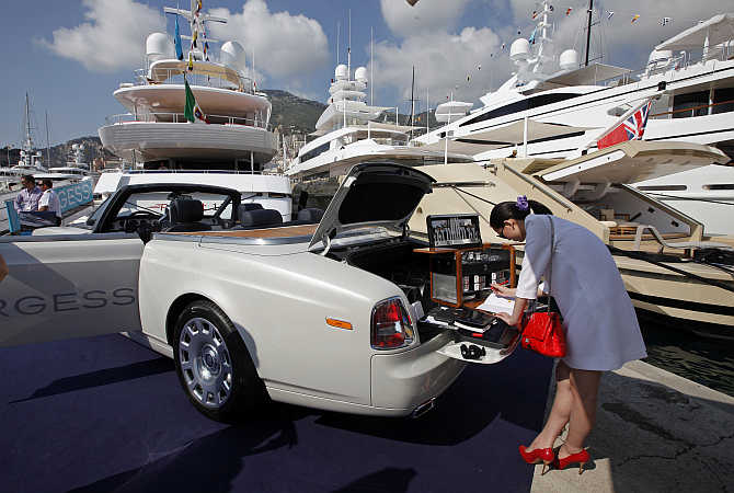 A visitor is seen next to a Rolls Royce parked on Monaco port.
