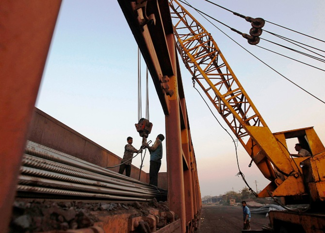 Workers prepare to unload steel rods with a crane from a goods train at a railway yard in Ahmedabad.