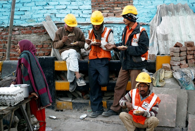 Labourers eat during a break from their work at the site of a commercial building under construction in Noida.