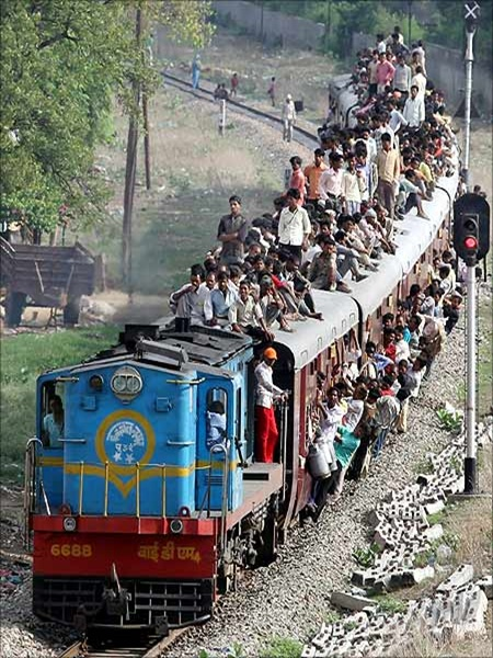 People travel on a crowded passenger train in Lucknow.