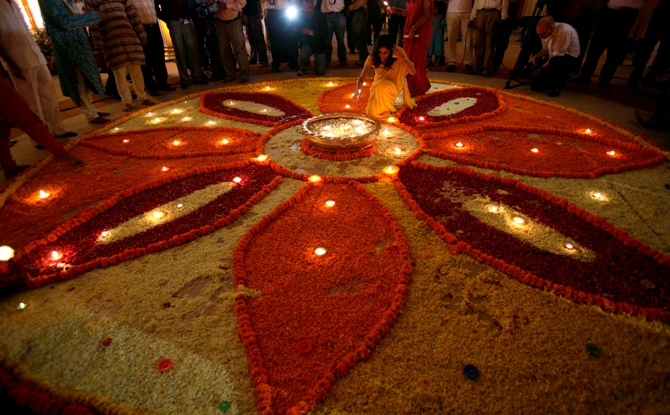 A woman lights up lamps in a flower decoration during Diwali mahurat special trading on the occasion of Diwali.