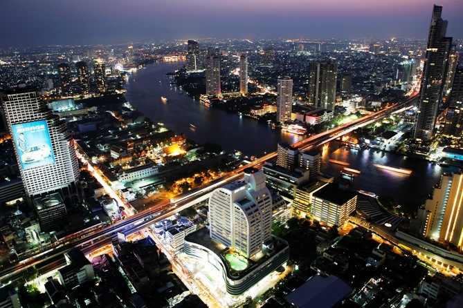 Cars and trains move on Taksin bridge over Chao Phraya river in central Bangkok at sunset.