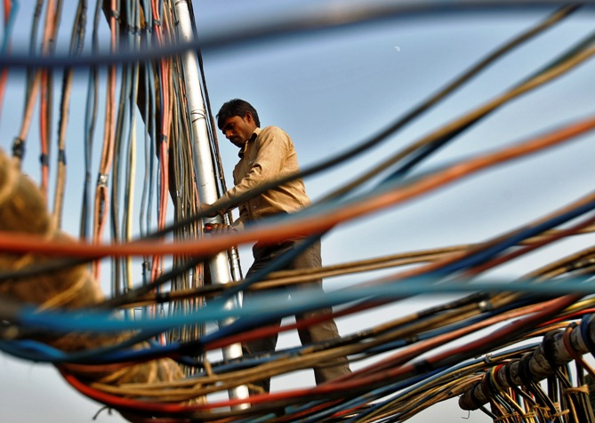 An electrician installs power cables outside the Indian Parliament building in New Delhi.