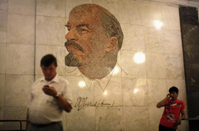 Men use their mobile phones as they stand in front of a mosaic depicting former Soviet leader Vladimir Lenin at Biblioteka Imeni Lenina metro station in Moscow.