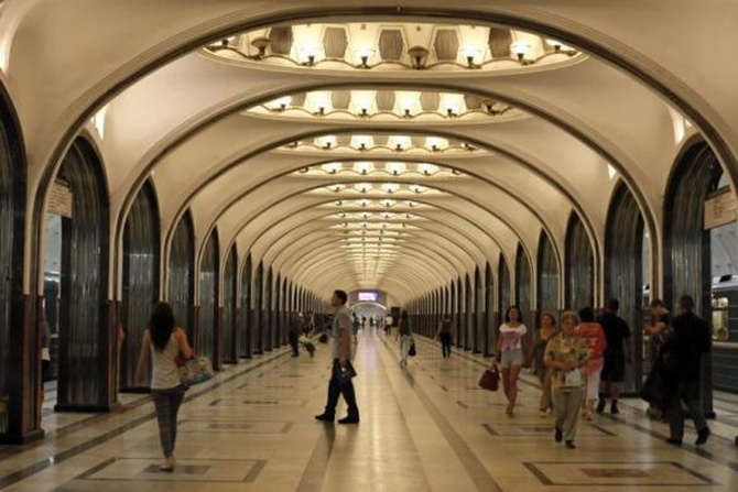 People wait for the train in Mayakovskaya metro station, which was built in 1938, in Moscow
