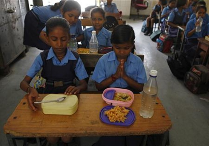A schoolgirl (C) prays before having her free mid-day meal, distributed by a government-run primary school, in New Delhi.