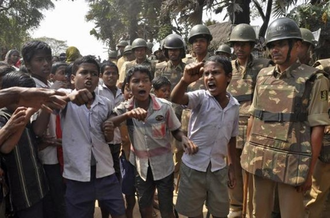 Children shout slogans as police stand guard during a protest against land acquisition at Gobindpur village in Jagatsinghpur district in Odisha.