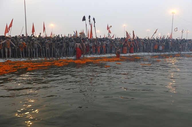 Priests prepare to take a holy dip during first Shahi Snan (grand bath) at the Kumbh Mela in Allahabad.