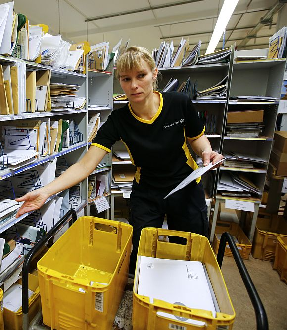 Sabine Standke, 32-year-old postwoman of the German postal and logistics group Deutsche Post, sorts mail at a sorting office in Berlin's Mitte district.