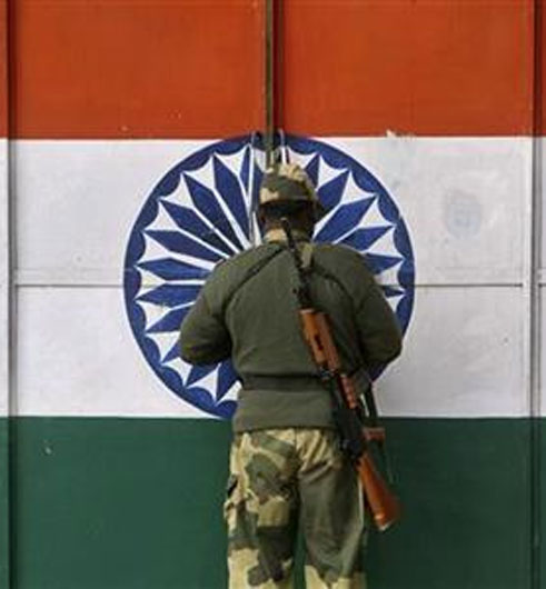 An Indian Border Security Force soldier opens a gate at the border with Pakistan near Jammu.