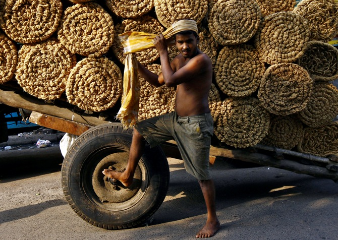 A labourer ties cloth around his head before unloading coir rolls at a wholesale market in Kolkata.