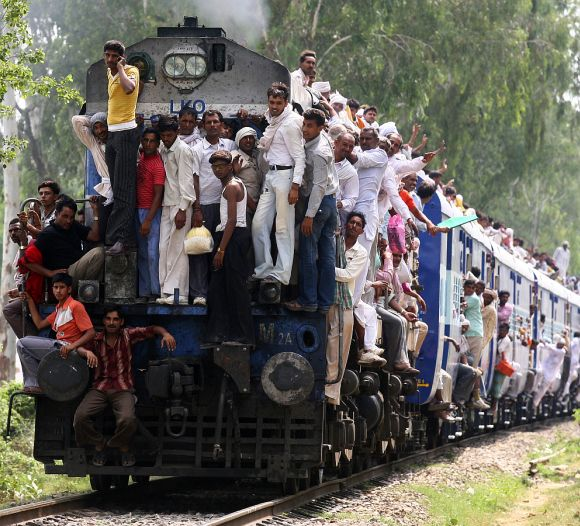 People travel in an overcrowded passenger train.