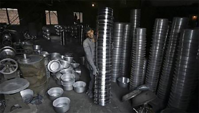 An employee works inside an aluminium utensil manufacturing unit.