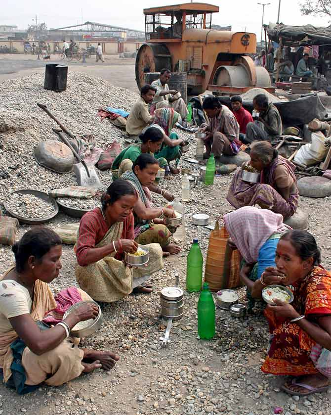 Road construction workers eat food during a break from work in Siliguri.