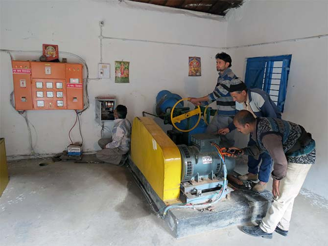 A trained grassroots engineer operates the turbine in electricity generation unit and maintains supply to the village.