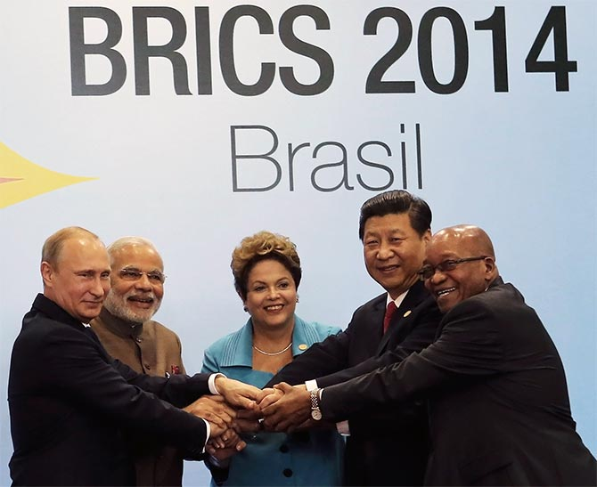 (L-R) Russian President Vladimir Putin, Indian Prime Minister Narendra Modi, Brazilian President Dilma Rousseff, Chinese President Xi Jinping and South African President Jacob Zuma join their hands at a group photo session during the 6th BRICS summit in Fortaleza.