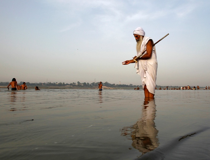A Sadhu offers milk to the waters of holy river Ganga as part of his morning prayers in Allahabad.