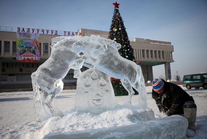A worker works on an ice sculpture of horses in front of a giant Christmas tree to celebrate Christmas at the Youth Theatre in Darkhan city, Mongolia.