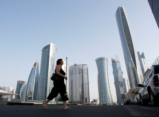 A woman crosses Al Wahda street hosting the Navigation Tower, headquarters of Qatargas (R), and Rasgas tower (2nd R) in Doha.