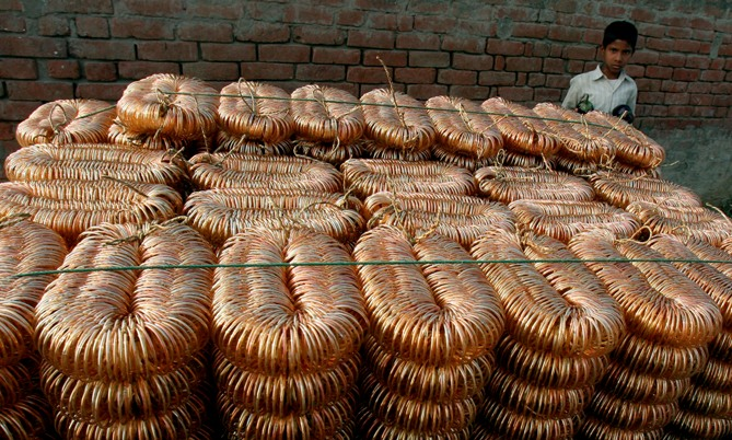 A boy stands beside a heap of joined bangles in Firozabad town, about 230 km (140 miles) southeast of New Delhi.