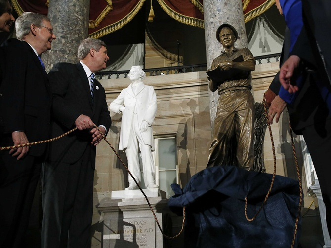 US Secretary of Agriculture Tom Vilsack (2nd L) and Senate Minority Leader Mitch McConnell (R-KY) (L) unveil a statue of Dr Norman E. Borlaug at Statuary Hall in the US Capitol in Washington.