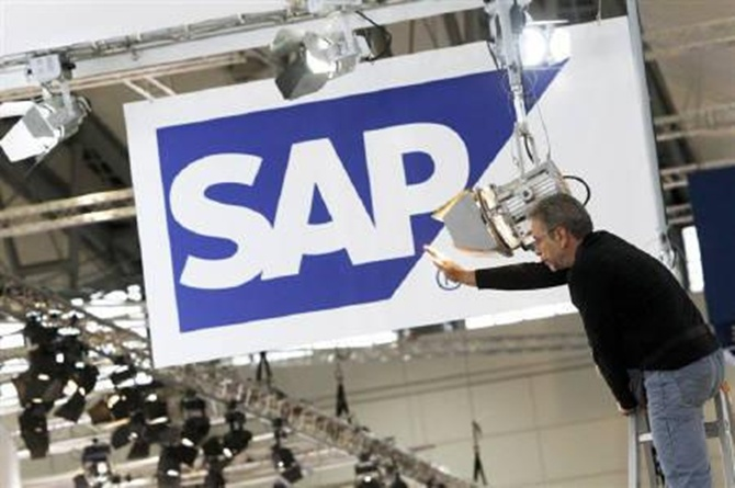 A worker adjusts a spotlight at the SAP booth in preparation for the CeBIT fair in Hannover.