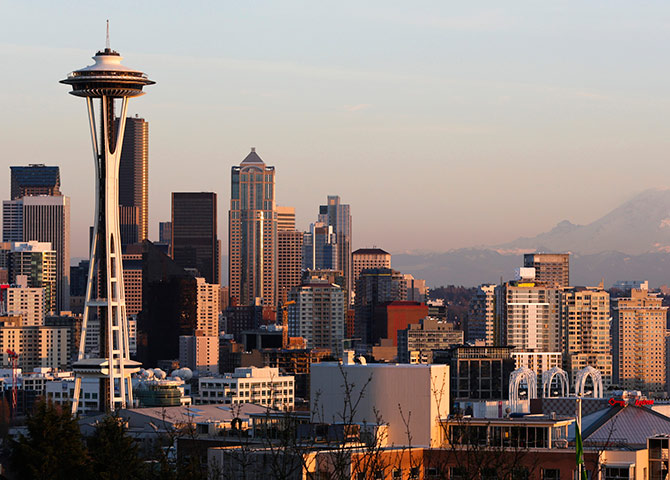 The Space Needle and Mount Rainier are pictured at dusk in Seattle, Washington.