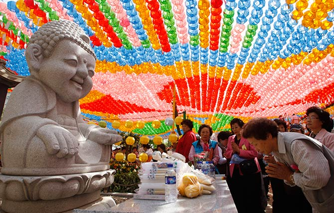 Buddhists pray in front of a statue of Buddha during a prayer meeting to celebrate the birth anniversary of Lord Buddha at the Jogye temple in Seoul.