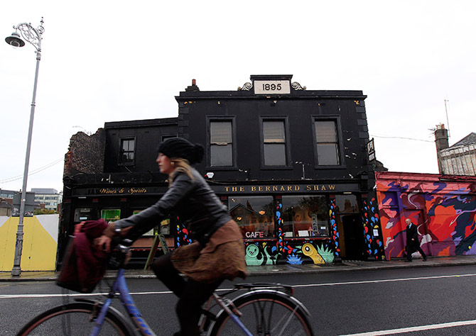 A woman cycles past the Coffee To Get Her restaurant near Dublin city centre which becomes a bar and club in the evenings.
