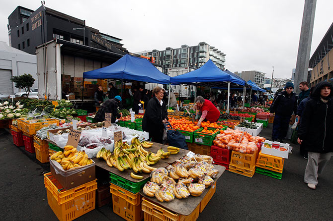 People buy fruits at a fruit and vegetable market in front of the Te Papa Museum in Wellington.