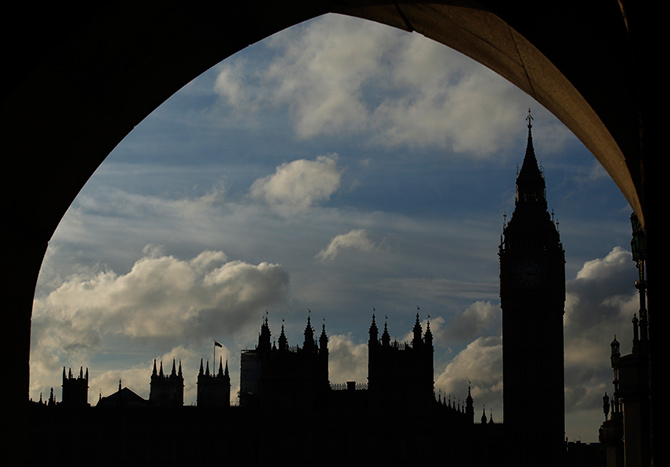 The Houses of Parliament and Big Ben are silhouetted against the sky in London.