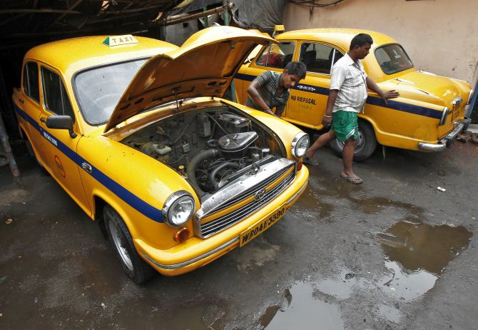 A mechanic repairs a yellow ambassador taxi at a workshop in Kolkata.