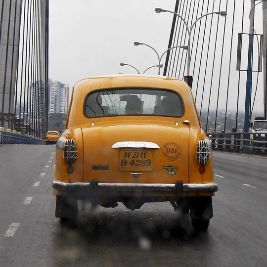 A yellow ambassador taxi crosses the Vidyasagar Setu bridge in Kolkata.